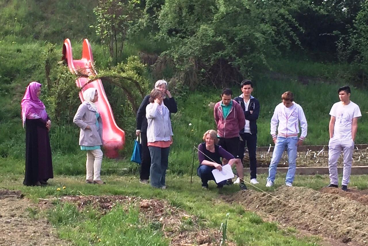 Flüchtlinge helfen bei der Gartenarbeit